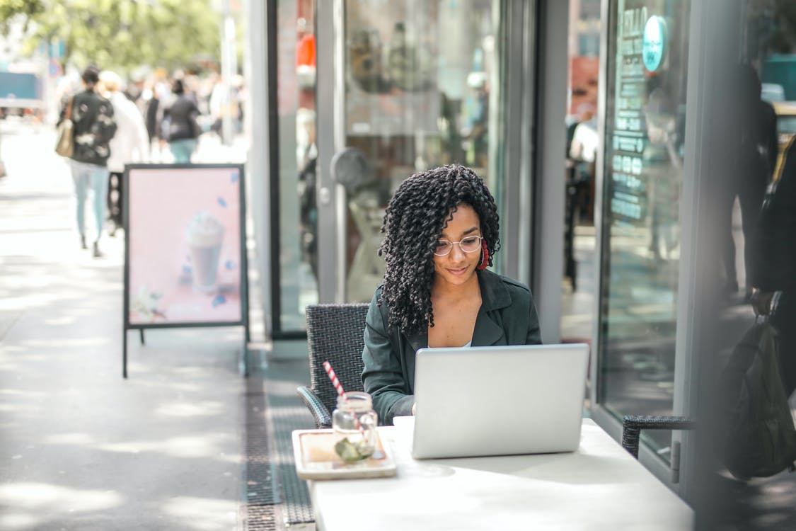 woman sitting at a cafe table on her computer