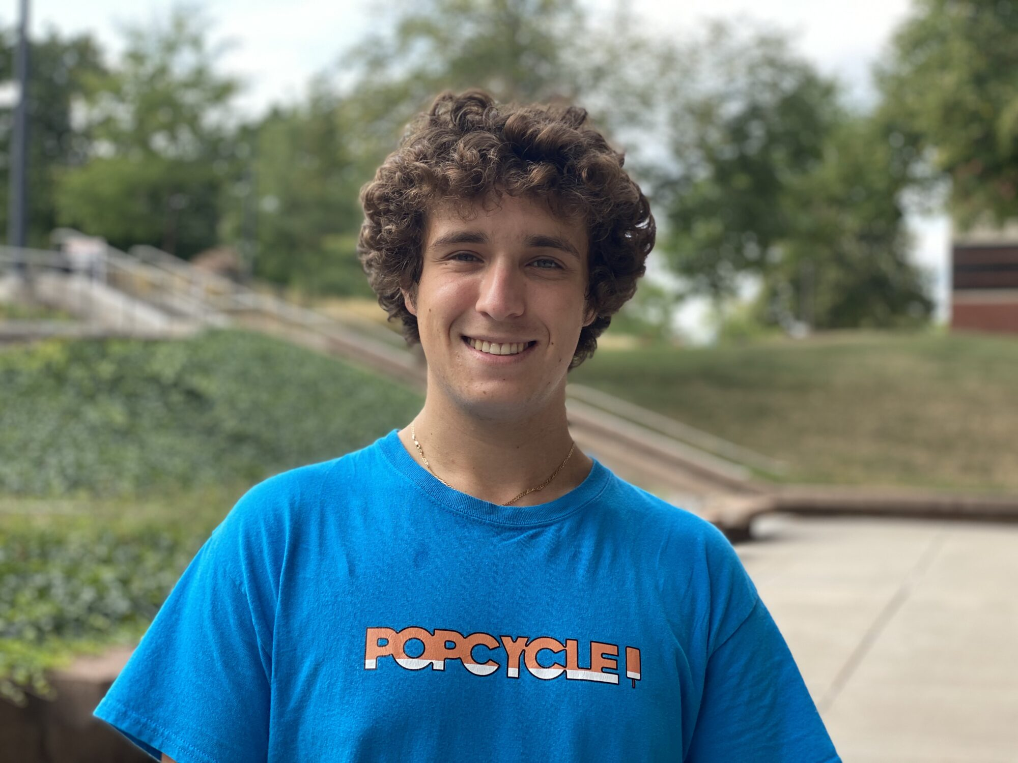 student in a blue POPCYCLE brand shirt