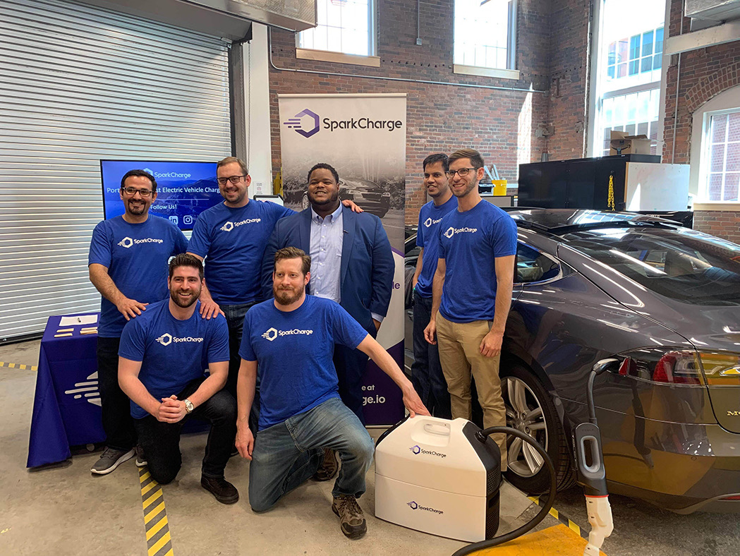 A team in blue SparkCharge shirts charging an EV