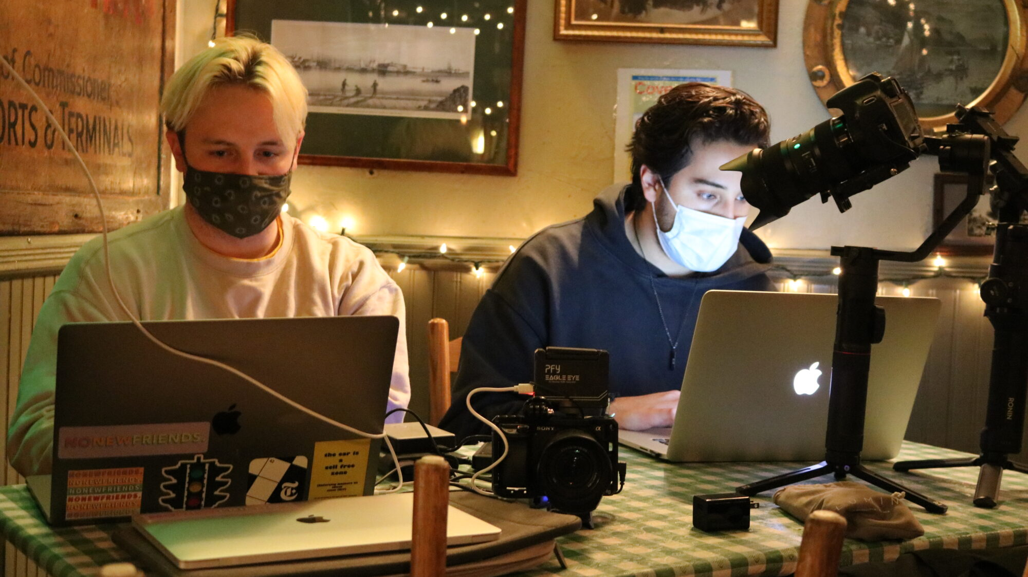 two digital content creators at laptops with video and sound equipment