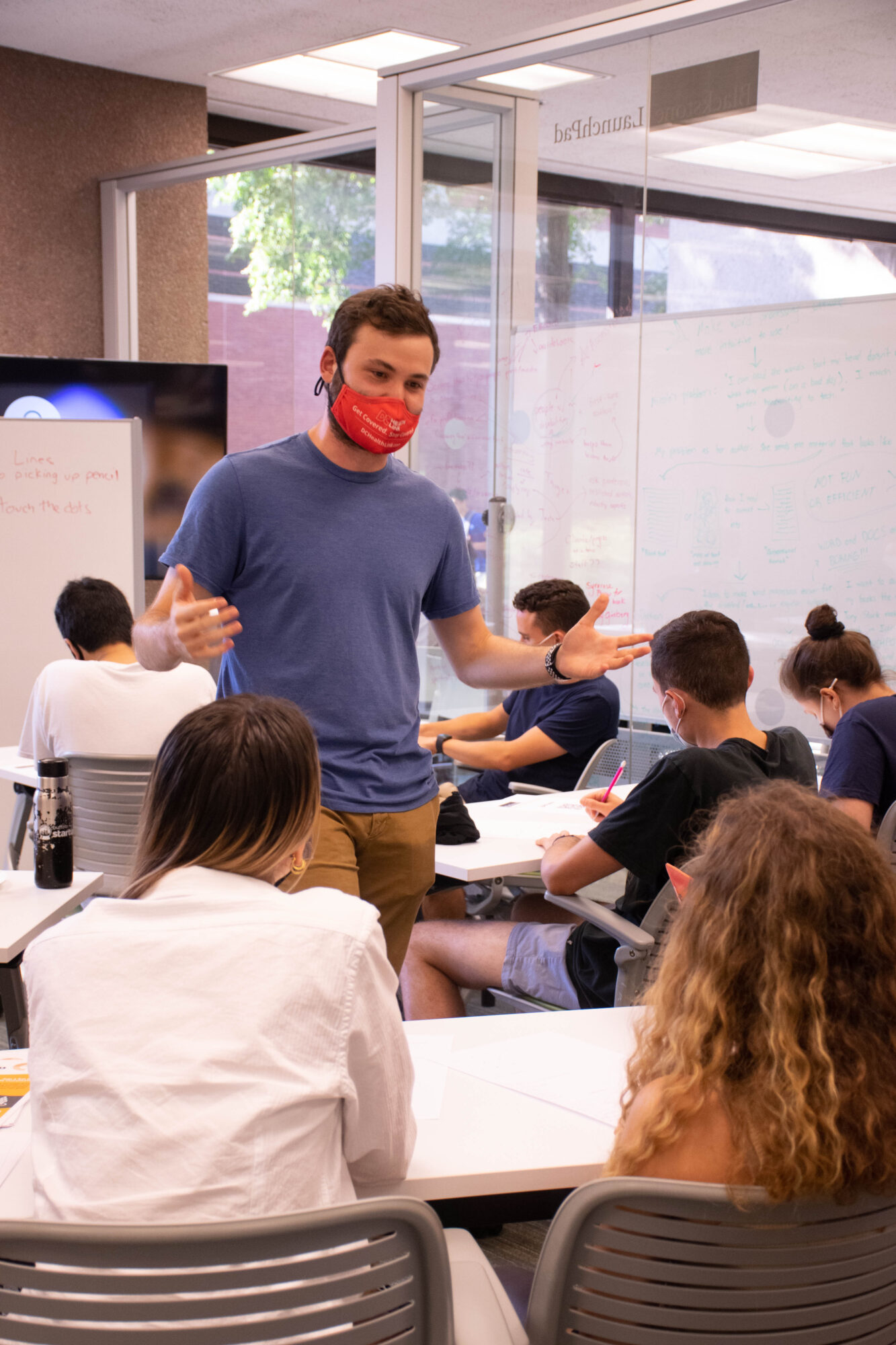 man talking to students in a workshop setting