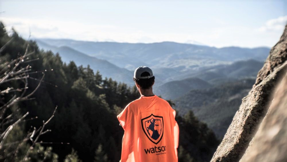 student on a hilltop looking at a mountain vista